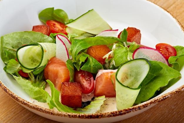 무 양상추와 함께 건강한 야채 샐러드는 흰 접시에 토마토와 오이를 남깁니다.