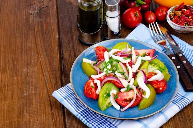 Здоровый овощной салат с помидорами и кусочками кальмаров. студийное фото.