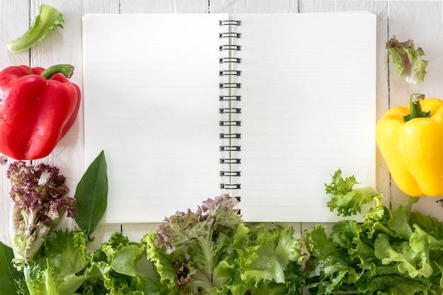 木製の背景に健康な野菜とメモの本