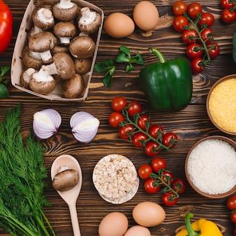 Здоровые овощи; яйца; воздушный пирог и полента на деревянном столе