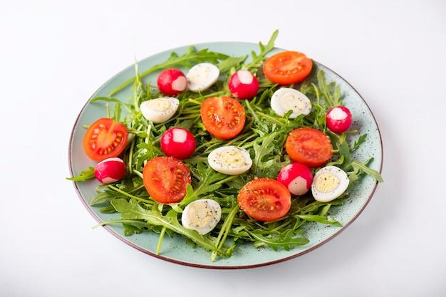 ヘルシーな野菜サラダをお皿に。トマト。卵、タディッシュ、ルッコラ。ダイエット食品のコンセプト。白い背景の上の新鮮なサラダ