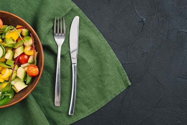 Healthy vegetables salad with fork and butterknife on tablecloth over black concrete backdrop