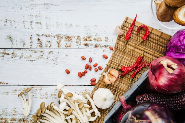 Healthy vegetables; spices; mushrooms and peanuts on placemat over wooden table