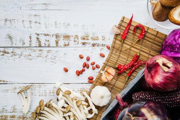 Verdure sane spezie; funghi e arachidi su placemat sopra tavolo in legno
