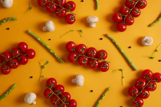 Healthy vegetables used for cooking purposes. ripe red cherry tomatoes, sprouts of asparagus, white champignons and peppercorns isolated on yellow background. products from grocery store or market