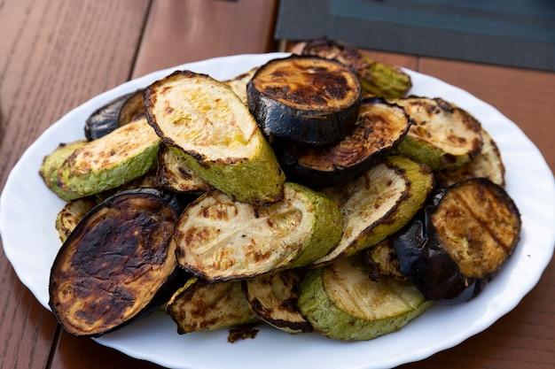 ヘルシーな野菜、ズッキーニ、焼きなすが白いお皿にのせます。セレクティブフォーカス。