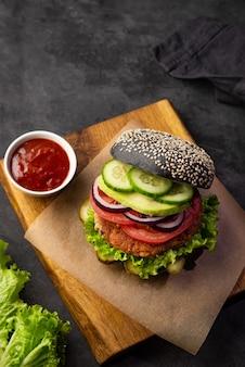 Здоровый вегетарианский черный бургер с соевой котлетой и овощами на разделочной доске на темном фоне. копировать пространство