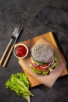 Healthy vegetarian black burger with vegetables ant tomato souce on a cutting board on a dark background. top view and copy space