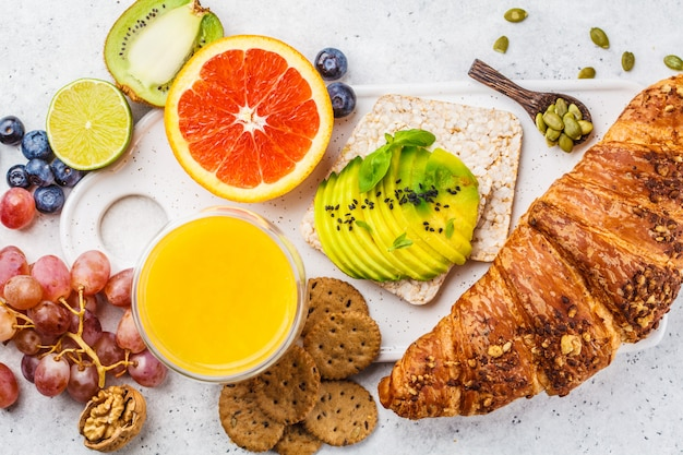 Healthy vegetarian breakfast with croissant, avocado toast, fruit and juice on a white plate.