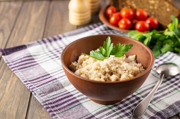 Здоровый вегетарианский завтрак с пшеничной кашей, хлебом, помидорами и петрушкой