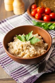 Здоровый вегетарианский завтрак с пшеничной кашей в миске, хлебом, помидорами и петрушкой