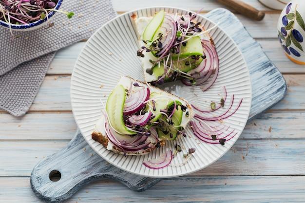 パン、マイクログリーン、チーズ、きゅうり、赤玉ねぎと健康的なベジタリアンブルスケッタ