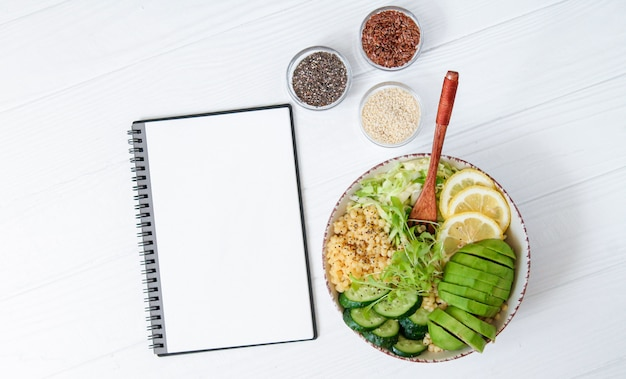 Healthy vegetarian buddha bowl with avocado couscous seeds and microgreen next to blank notebook for recipe top view