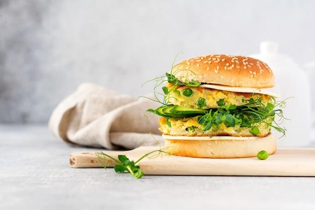 卵とエンドウ豆の芽と種子のマイクログリーン、新鮮なサラダ、明るい背景のカッティング木の板にキュウリのスライスと健康的なベジタリアンバーガー。セレクティブフォーカス