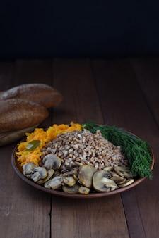 Здоровая вегетарианская фитнес-еда. гречка с овощами, грибами и зеленью. подается на глиняной тарелке.