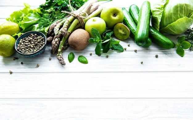 健康的なベジタリアン料理のコンセプトの背景、デトックスダイエット、リンゴ、キュウリ、アスパラガス、アボカド、ライム、白い木製の背景のサラダ上面図の新鮮な緑の食品の選択