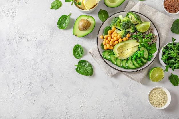 健康的なベジタリアン料理のコンセプト:白い背景に野菜、種子、ハーブとキノア。上面図。