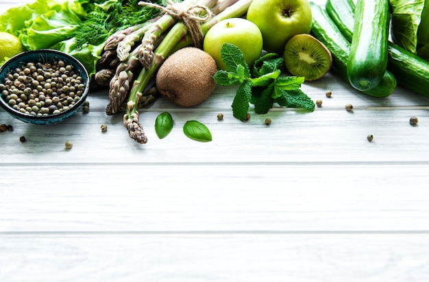 Healthy vegetarian food concept surface, fresh green food selection for detox diet,  apple, cucumber, asparagus, avocado, lime,  salad  top view on a white wooden  surface