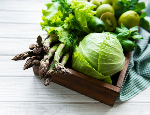 Healthy vegetarian food concept surface, fresh green food selection for detox diet, box with  apple, cucumber, asparagus, avocado, lime,  salad  top view on a white wooden  surface