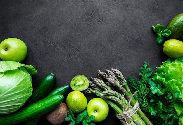 健康的なベジタリアンフードコンセプトサーフェス、デトックスダイエット、リンゴ、キュウリ、アスパラガス、アボカド、ライム、黒いコンクリート表面のサラダトップビューの新鮮な緑の食品の選択