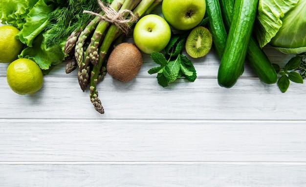 健康的なベジタリアンフードコンセプトサーフェス、デトックスダイエット、リンゴ、キュウリ、アスパラガス、アボカド、ライム、白い木製の表面にサラダトップビューの新鮮な緑の食品の選択