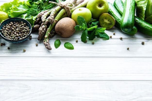 健康的なベジタリアン料理のコンセプトの表面、デトックスダイエットのための新鮮な緑の食品の選択、リンゴ、キュウリ、アスパラガス、アボカド、ライム、白い木の表面のサラダ上面図