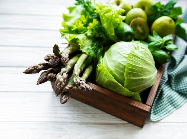 ヘルシーなベジタリアンフードコンセプトサーフェス、デトックスダイエット、アップル、キュウリ、アスパラガス、アボカド、ライム、白い木製の表面にサラダトップビューのボックスの新鮮な緑の食品の選択