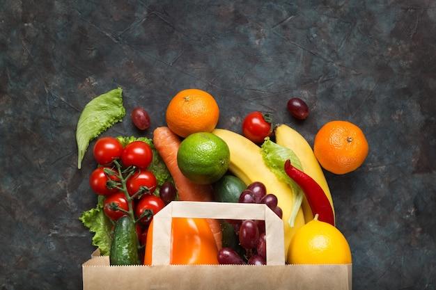 Здоровая вегетарианская еда в бумажном пакете с овощами и фруктами на темноте
