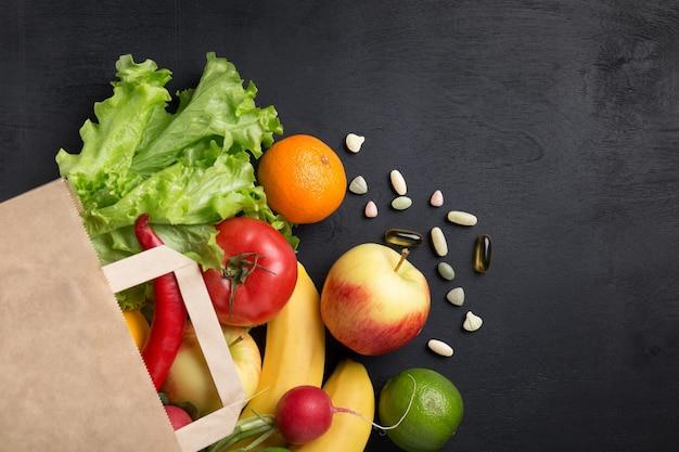 紙袋の野菜や果物の健康的なベジタリアン料理
