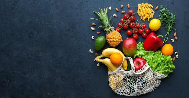 끈 가방에 건강한 채식 음식. 다양한 야채와 과일