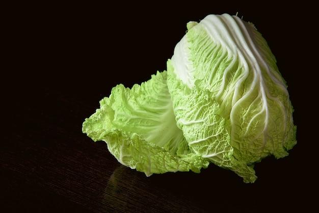 Здоровая вегетарианская пища, органическая пекинская капуста на темноте.