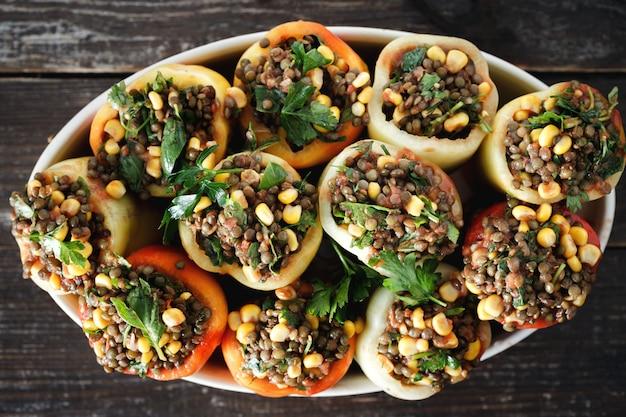 Healthy vegetarian food raw green lentils corn salsa stuffed peppers top view