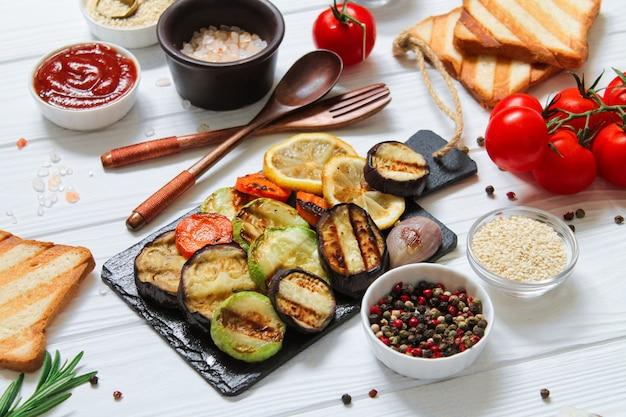 Здоровый вегетарианский стол на гриле с барбекю безглютеновым хлебом и овощами (цуккини, баклажаны, морковь, лимон)