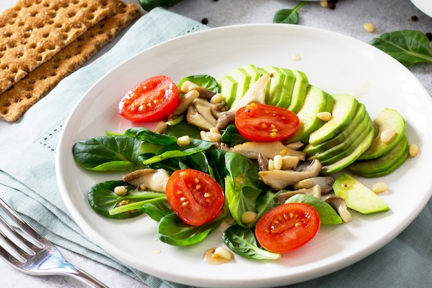 건강한 채식 점심 그릇 아보카도 버섯 체리 토마토 잣 시금치와 비네 그레트 소스 드레싱