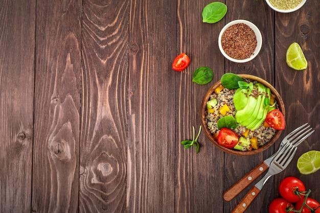 キノア、アボカド、トマト、ほうれん草、木製の背景に種子と健康的なベジタリアンランチボウル。上面図。スペースをコピーします。