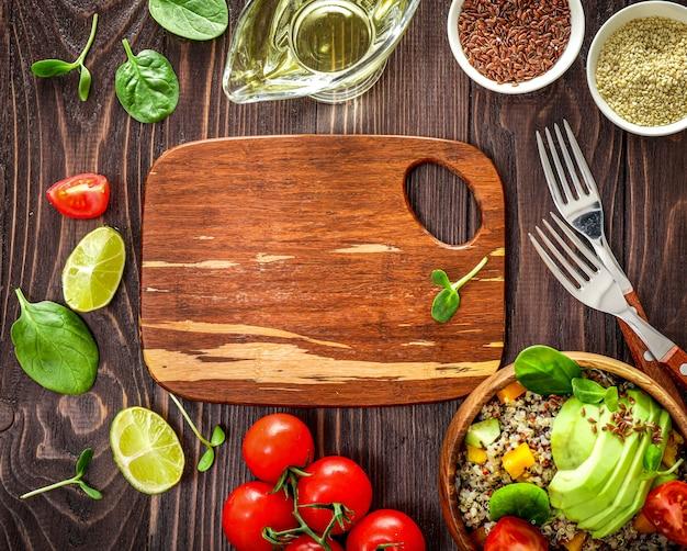 キノア、アボカド、トマト、ほうれん草、木製の背景に種子と健康的なベジタリアンランチボウル。上面図。