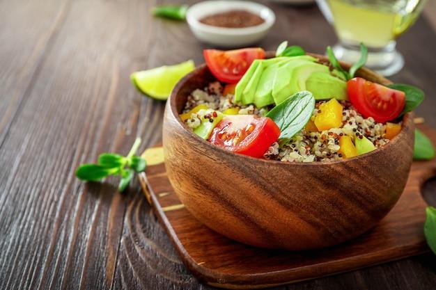 キノア、アボカド、トマト、ほうれん草、木製の背景に種子と健康的なベジタリアンランチボウル。