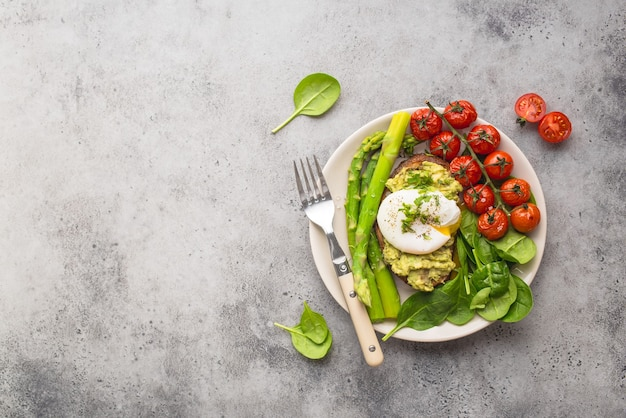 Здоровая вегетарианская тарелка. тост, авокадо, яйцо-пашот, спаржа, запеченные помидоры, шпинат.