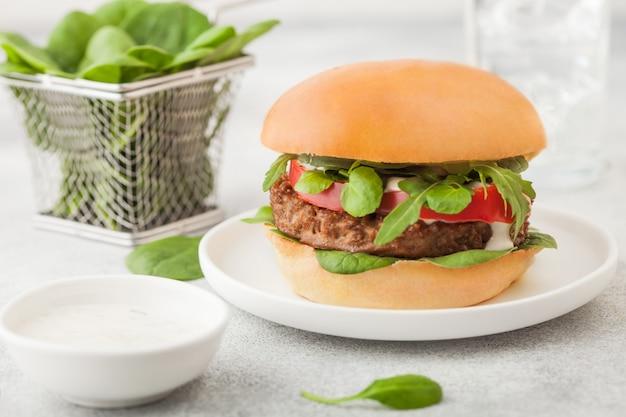 明るい背景に野菜とほうれん草と丸いセラミックプレート上の健康的なベジタリアン肉フリーハンバーガー。