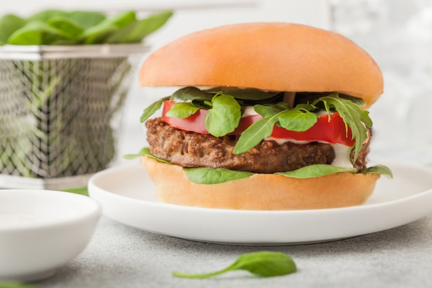ライトテーブルに野菜とほうれん草を添えた丸いセラミックプレートにヘルシーなベジタリアンミートフリーハンバーガー。
