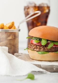 ポテトウェッジとコーラのガラスと明るい背景の野菜と丸まな板の健康的なベジタリアン肉フリーハンバーガー。