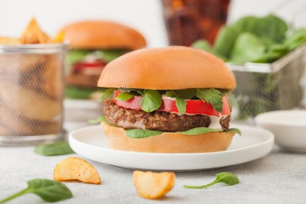 ポテトウェッジとコーラのグラスとライトテーブルの上の野菜と丸いセラミックプレート上の健康的なベジタリアンミートフリーハンバーガー。