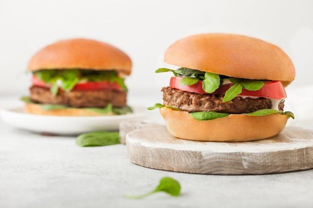 明るい背景に野菜とほうれん草をまな板に載せたヘルシーなベジタリアン肉フリーハンバーガー。