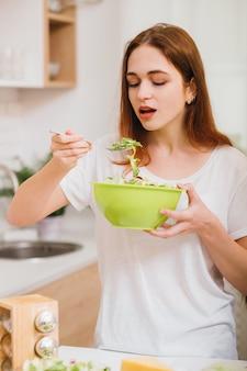 健康的な菜食主義の栄養。女性の食生活。新鮮なサラダを味わう魅力的な若い女性。