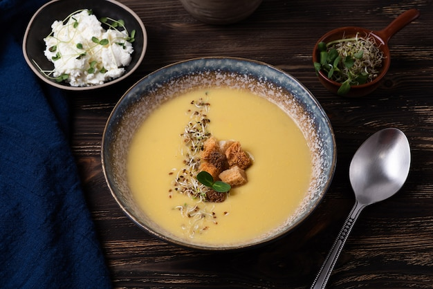 Healthy vegetarian puree soup, plate of squash cream soup with croutons, cheese and microgreens on a dark wooden background.