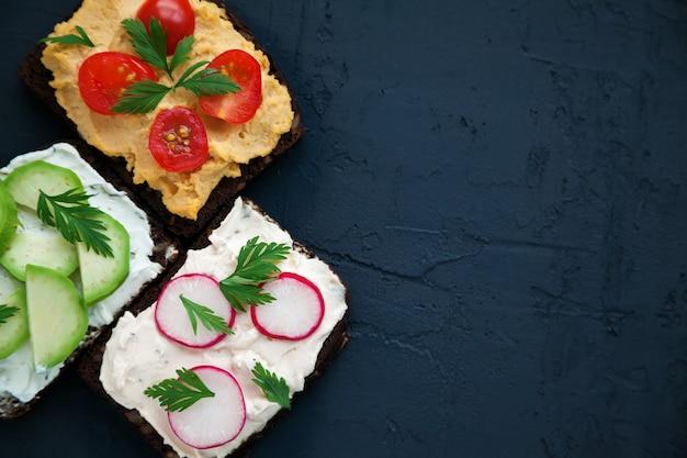 Полезные вегетарианские бутерброды из ржаного хлеба с творогом, хумусом, авокадо, редисом и помидорами. черный фон, копия пространства, вид сверху