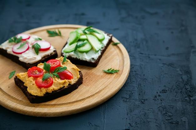 Полезные вегетарианские бутерброды из ржаного хлеба с творогом, хумусом, авокадо, редисом и помидорами. деревянная доска на черной поверхности, copy-space