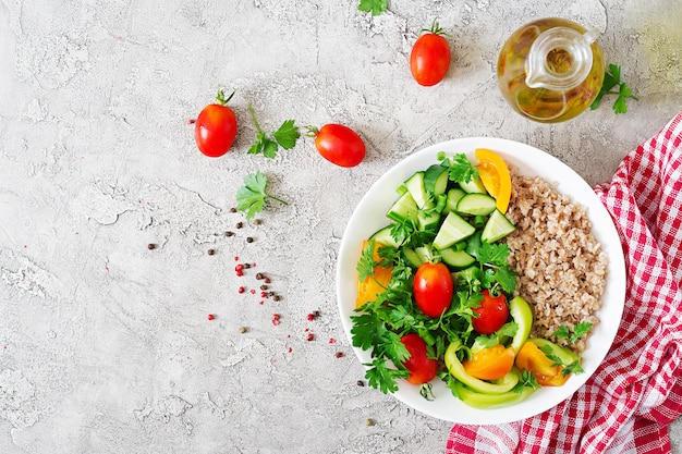 Healthy vegetarian salad of fresh vegetables, tomatoes, cucumber, sweet peppers and porridge