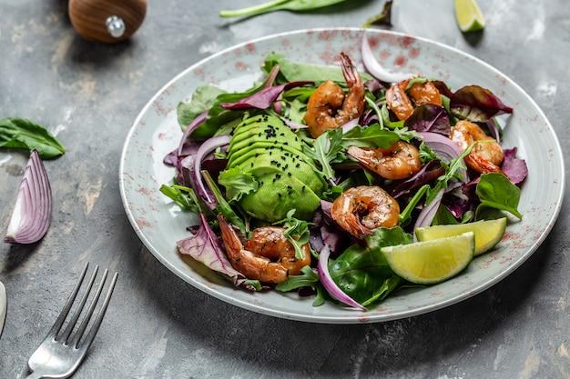 Здоровый вегетарианский салат с салатом из авокадо и креветок. концепция морепродуктов. вкусные овощи смешанные листья, креветки на гриле, вид сверху.