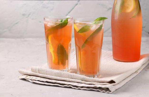 ライトグレーのテーブルにミント、レモン、氷を添えた健康的なビタミンルバーブとイチゴの夏の飲み物